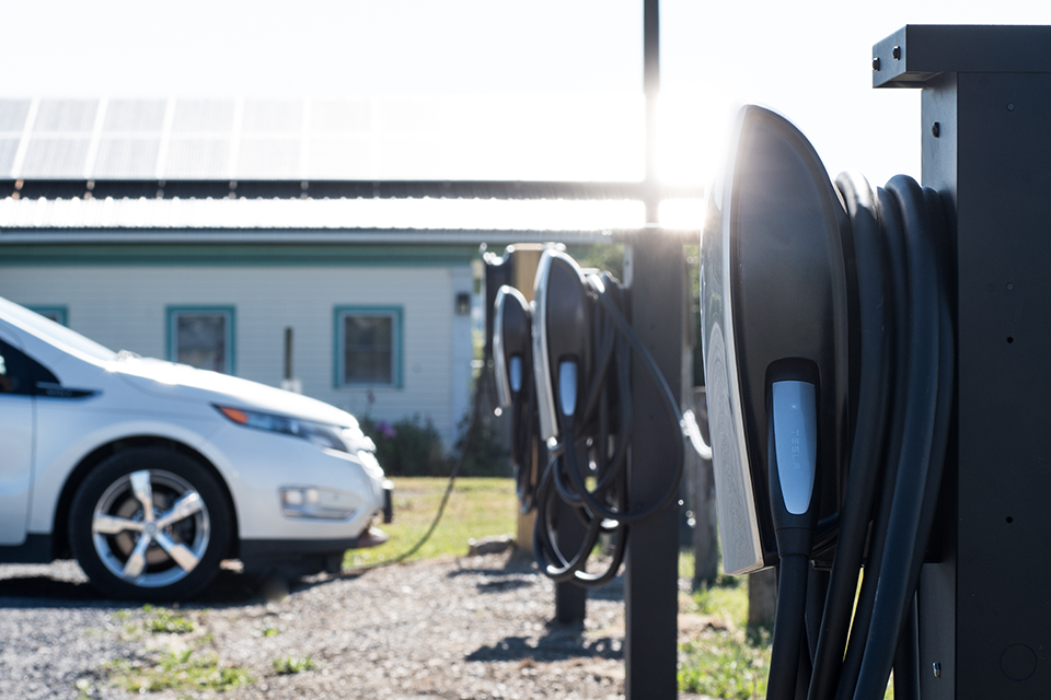 Car plugged into electric vehicle chargers in front of solar panels.