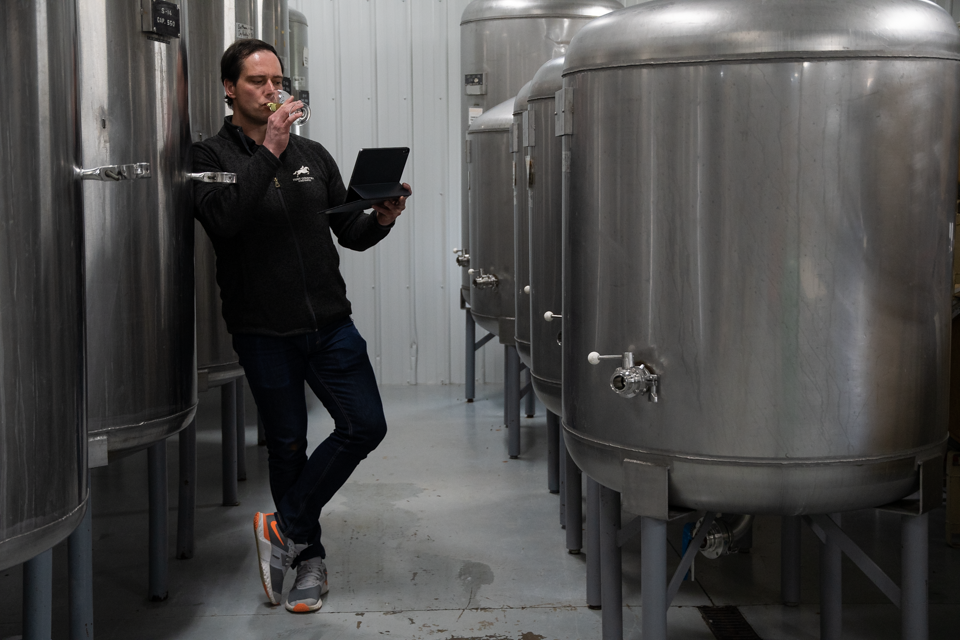 Image of Karsten sipping wine in winery.