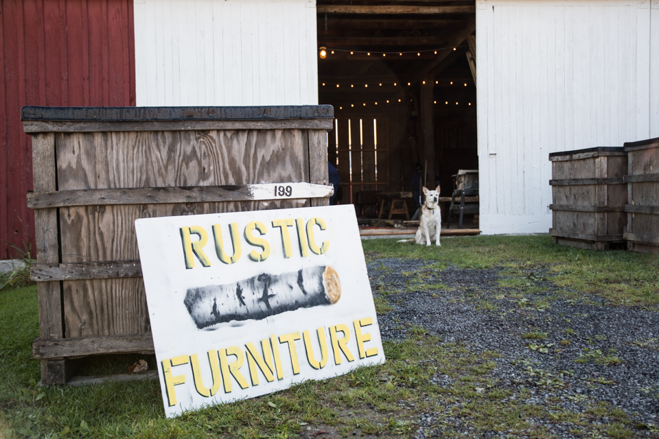 Image of sign, barn, with dog sitting in front.